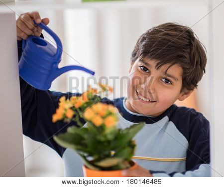 Child watering plants at home living room