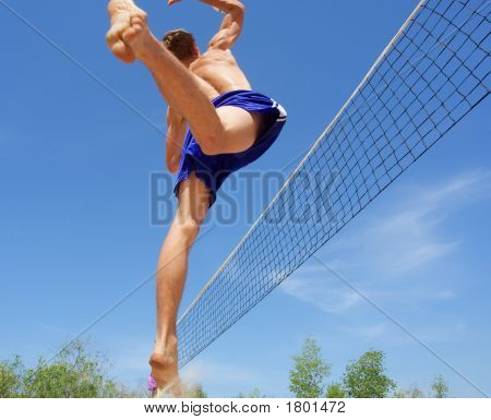 Teenager Playing Beach Volleyball - Jumps High To Spike The Ball