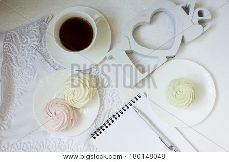 Zephyr, cup of coffe and notebook. Top view of notebook ,coffee , zephyr on white background