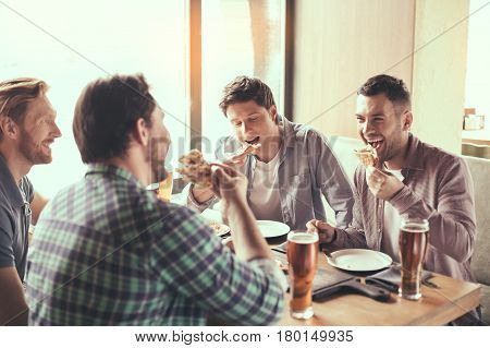 Pizza time. Friends spending time together in restaurant. Guys drinking beer and eating pizza