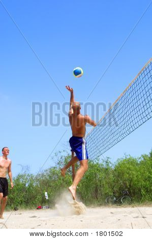 Two Men Playing Beach Volleyball - Balding Man Jumps High To Catch Ball