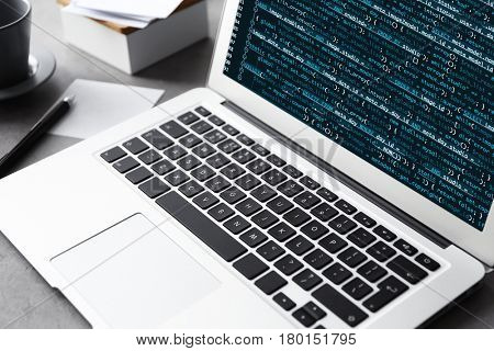 Laptop of programmer with script code on display