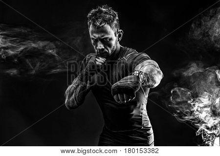 Studio portrait of fighting muscular man in smoke on black background