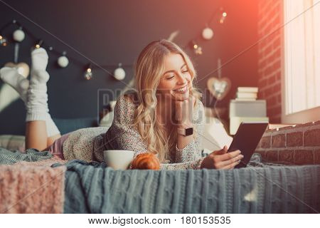Beautiful young woman lying on the bed with the tablet and hot drink.