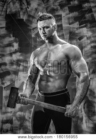 athlete and hammer. guy with a nice toppless muscle fitness body, bodybuilder coach hold big metal hammer
