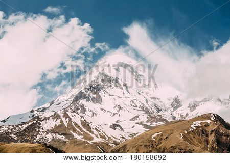 Peak Of Mount Kazbek Covered With Snow. Kazbek Is A Stratovolcano And One Of Major Mountains Of Caucasus Located On Border Of Georgia's Kazbegi District And Russia's Republic Of North Ossetia Alania