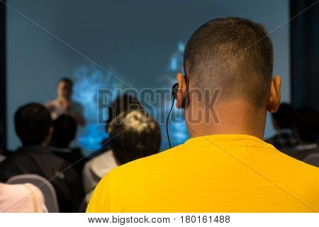 The Male Audience At International Business Meeting Or Seminar Wearing Headphone For Online Translat