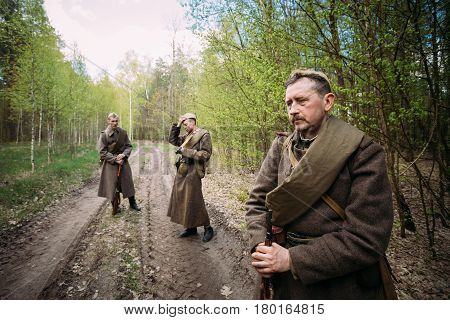 Pribor, Belarus - April 23, 2016: Re-enactors Dressed As Russian Soviet Infantry Red Army Soldiers Of World War Ii Stopped To Rest During A Campaign In Forest