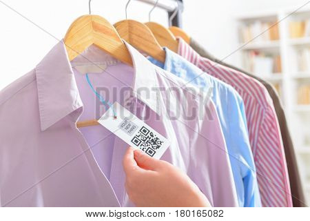 Woman's hand with a cloth label with QR code  in a shop