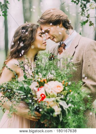 The beautiful and emotional close-up portrait of the newlywed couple standing head-tohead to each other and are under the rain of petals. The bride is holding the huge red, ahite and green bouquet
