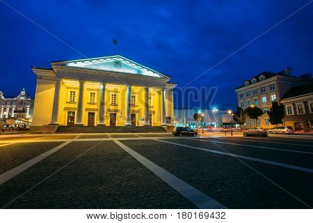 Vilnius, Lithuania. Main Facade Of Town Council In Evening Illumination, Administrative Building With Columns On Didzioji Street In Old Town Under Summer Blue Sky.