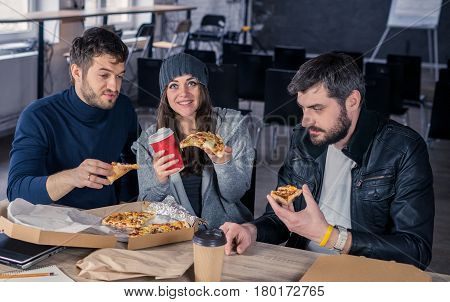 Business team eating pizza and drinking in office. Woman is giving pizza to camera. Working environment with laptop coffee notepads and stationery.