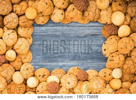 Cookies frame background. Sweet chocolate chips biscuits on blue rustic wood with copy space.