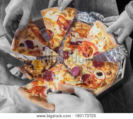 Black and white top view of hands taking pizza. Concept of friendship at work unity teamwork partnership.