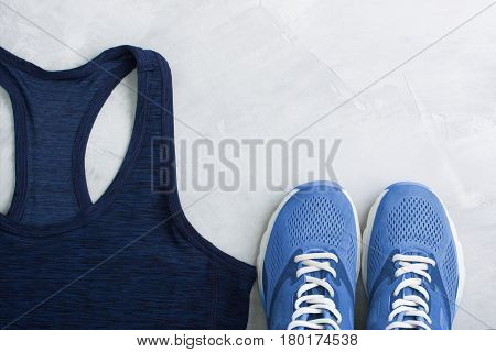 Flatlay sport composition with blue sneakers and t-shirt on gray concrete background. Concept healthy lifestyle sport training in gym diet. Horizontal orientation top view place for copyspace.