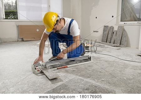 Construction worker wearing bib overalls and hard hat cutting ceramic tiles using ceramic cutter.