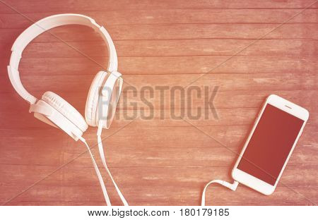 White phone and headphones flat lay on wooden table. Warm orange light toned photo. Smartphone and earphones vintage banner template with text place. Music listening concept image. Black screen phone