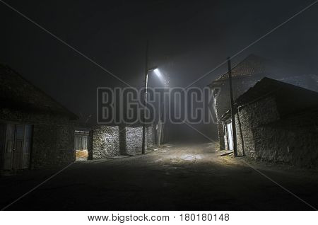 Night Street Country Road With Buildings And Fences Covered In Fog Lamp . Or Mysterious Night In The