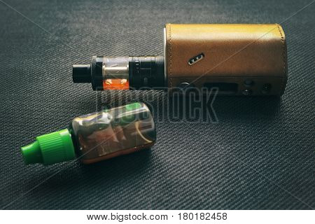 Vape. Bottle With E-liquid And Nicotine And Electronic Cigarette Mod On Black Textile. Personal Vapo