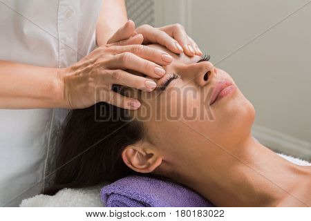 Face lifting massage to beautiful girl in cosmetology cabinet or beauty parlor.