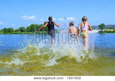 Three Kids, Two Girls And Boy, Run Into In Water With Splashes