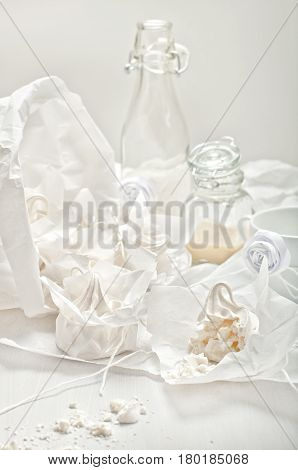 High key still life with meringues crumbs glass jars and cup with milk and paper roses