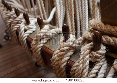 Hemp ropes tied to wooden beams part of the rigging system of old sailboat controlling sails.