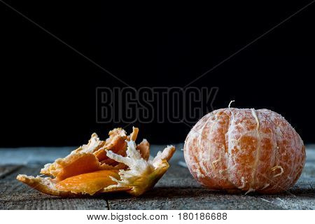 Mandarin on old wooden table in old kitchen black background