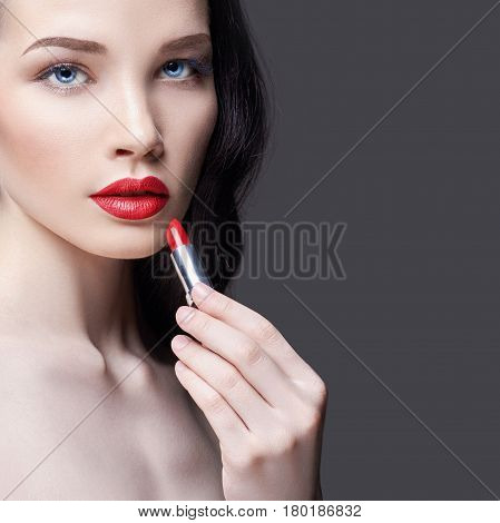 Young brunette woman paints her lips bright red lipstick. Bright evening makeup. Naked girl taking care of her face and lips