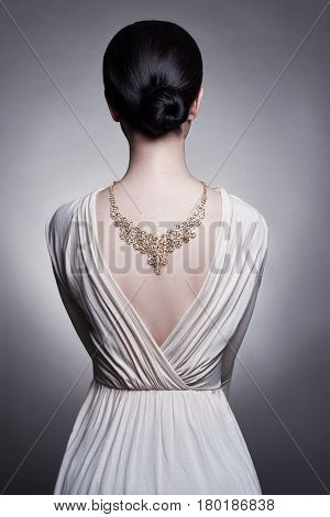 Jewels on the girl's neck beautiful gold necklace. Brunette in evening dress with necklace back. Skin care. Perfect beautiful sexy woman. Lady in a light summer dress