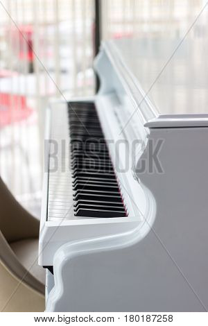 White piano with black keys near the window