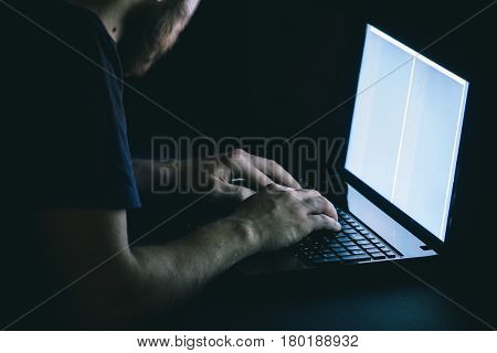 The hacker hacks the server with bank accounts in a dark room on a black background in the dark. The concept of cyber attacks and the Cold War on the Internet