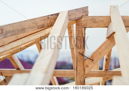 Details Of Construction Site, Timber Structure Of Truss Roof System. The Wooden Structure Of The Bui