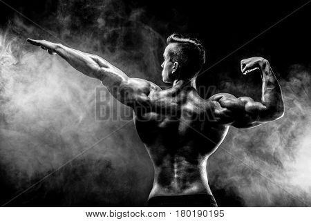 Unrecognizable man with strong muscles posing with arm up in smoke.