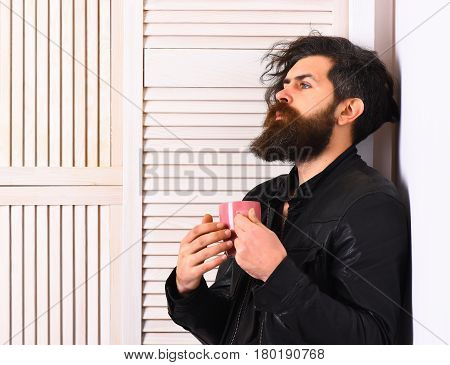 Bearded man long beard. Brutal caucasian hipster with moustache and ruffled hair holding cup or mug in rock black style on white wooden vintage studio background