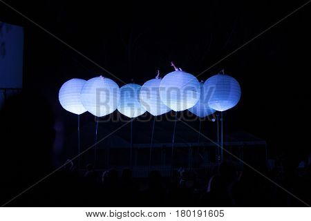 Canberra, Australia-September 27, 2009. Outdoor performance at night with acrobats moving inside giant paper lanterns.