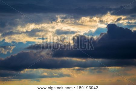 Stormy sky with rays of sunlight. Sunset scene with rainy clouds. Tropical sunset romantic photo banner. Fluffy clouds with sun reflections. Orange sunlight on grey clouds. Rainy season weather