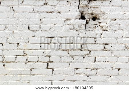 Old white brick wall with holes. Abstract background