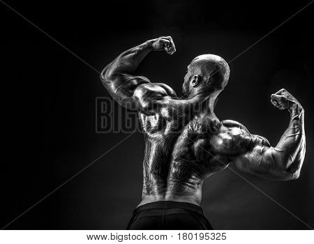 unrecognizable tattoed bodybuilder with outstretched arms on black background. Isolated.