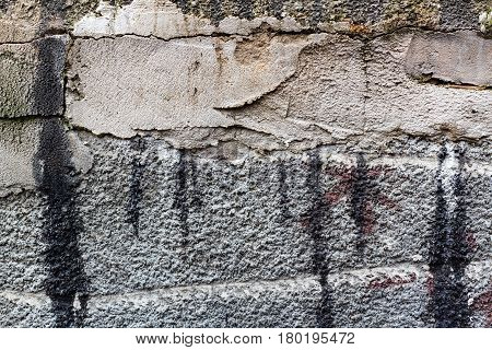 Concrete wall with traces of repair and the stains of bitumen mastic. Abstract background
