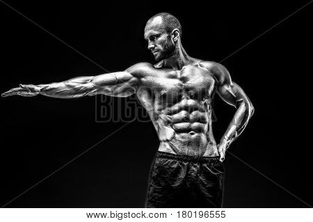 Strong bald bodybuilder with six pack. Strong bodybuilder man with perfect abs, shoulders, biceps, triceps and chest, personal fitness trainer flexing his muscles