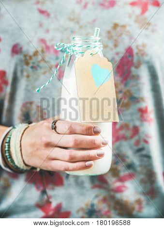 Young woman in grey t-shirt with floral pattern holding bottle of dairy-free almond milk in her hand. Clean eating, vegan, vegetarian, dieting, healthy food concept