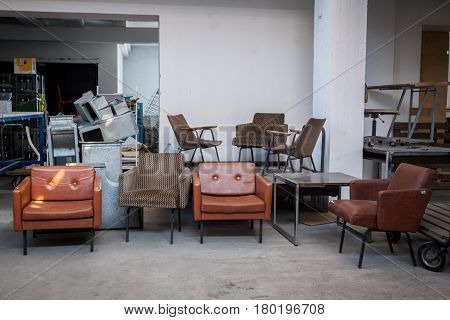 Vintage leather armchairs from the 70's for sale in the warehouse of an antique dealer in a flea market Picture of old armchairs from the 70's stored in the hall of a flea market