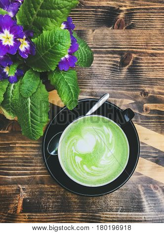 Cup of matcha latte and bright flowers on wooden table, top view, vertical composition
