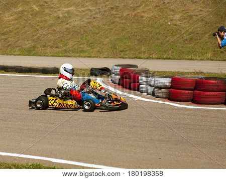 ODESSA UKRAINE - APRIL 2 2017: Competitions on the picture pilots in helmet and in racing clothes participate in the card race. Carting show. Children and adult racers on bright branded maps.