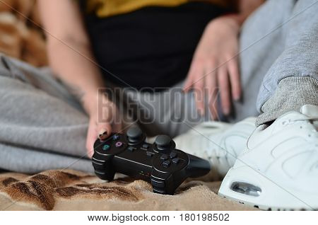 Modern Black Game Controller In The Hands Of A Seated Young Girl