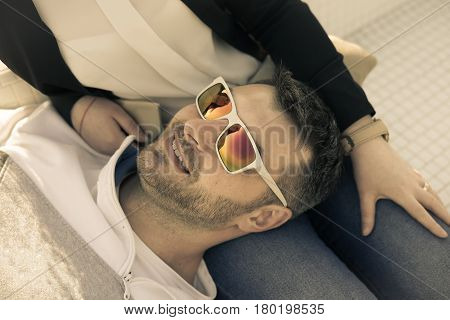 Smiling happy bearded man wearing Colorful sunglasses lying on his girlfriend. Girlfriend is in the reflection of the glasses.