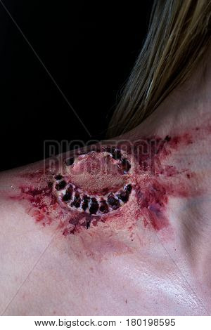 Fresh bloody bite from a zombie or monster on a shoulder of blonde woman. Scarry scene.