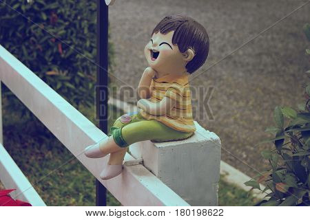 dolls decoration in the garden laughing happyness the doll sitting on a white fence. for decorate in the garden