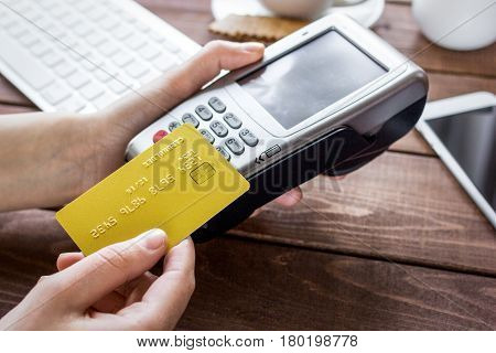 Payment for breakfast in cafe with keyboard and telephone, credit card and terminal on wooden table background